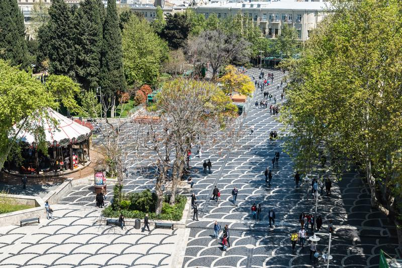 View over Fountains Square in Baku, Azerbaijan. Baku, Azerbaijan - April 27, 2019. Fountains Square in Baku, with buildings, vegetation and people stock image