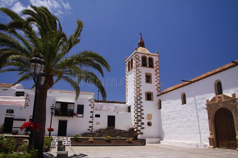 BETANCURIA, FUERTEVENTURA - JUIN 14. 2019: View over garden with palm trees on old white church with clock tower against blue sky stock photo