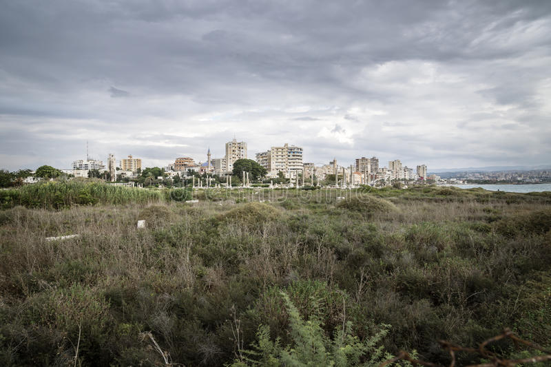 View over grassland to cityscape and ruins with dramatic cloudscape in Tyre, Sour, Lebanon royalty free stock image
