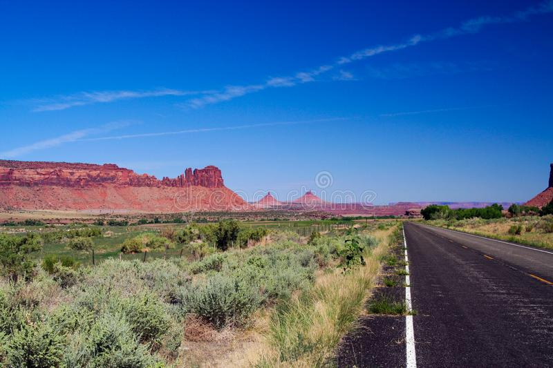 View over green valley on endless straight road with steep red sandstone hill formation butte against blue sky. Monument Valley, Utah, Arizona stock photography
