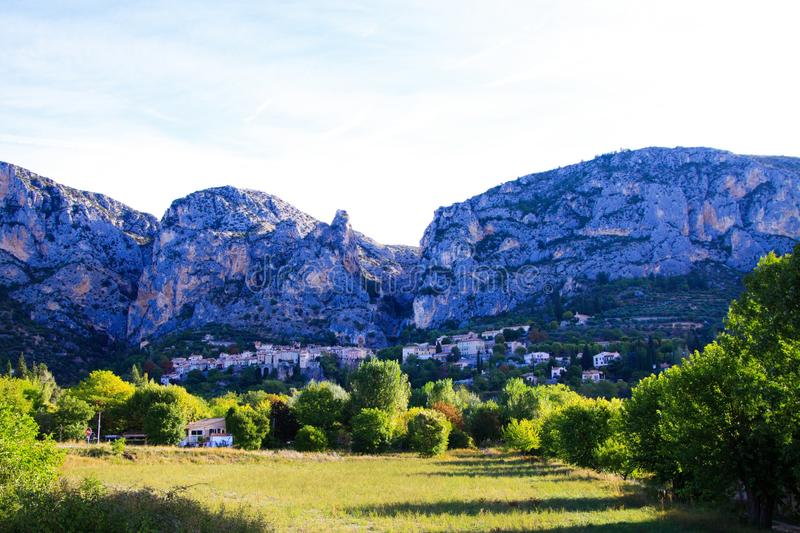View over green valley on French village with giant mountain face background in early morning - Moustiers Sante Marie, Provence,. France stock photography
