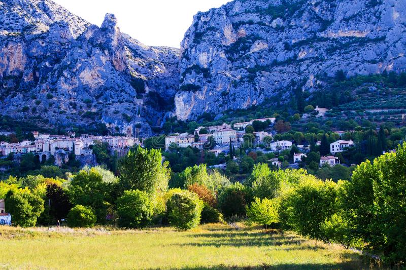 View over green valley on French village with giant mountain face background in early morning - Moustiers Sante Marie, Provence,. France royalty free stock photo