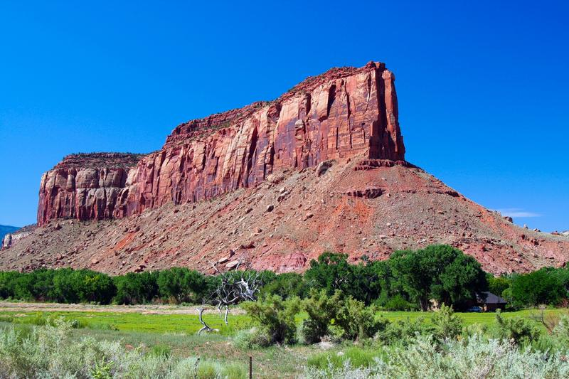 View over green valley on isolated steep red sandstone hill formation butte against blue sky  - Monument Valley. Utah, Arizona stock photography
