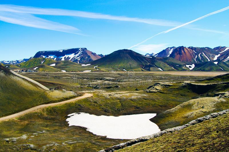 View over green valley mountain range and volcano cone with spots of snow and ice contrasting with blue cloudless sky. Landmannalaugar, Iceland royalty free stock images