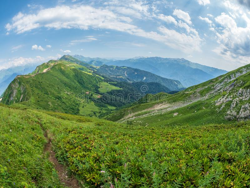 View over the Green Valley, surrounded by high mountains on a clear summer day. Krasnaya Polyana, Sochi, Caucasus. View over the Green Valley, surrounded by high royalty free stock photo