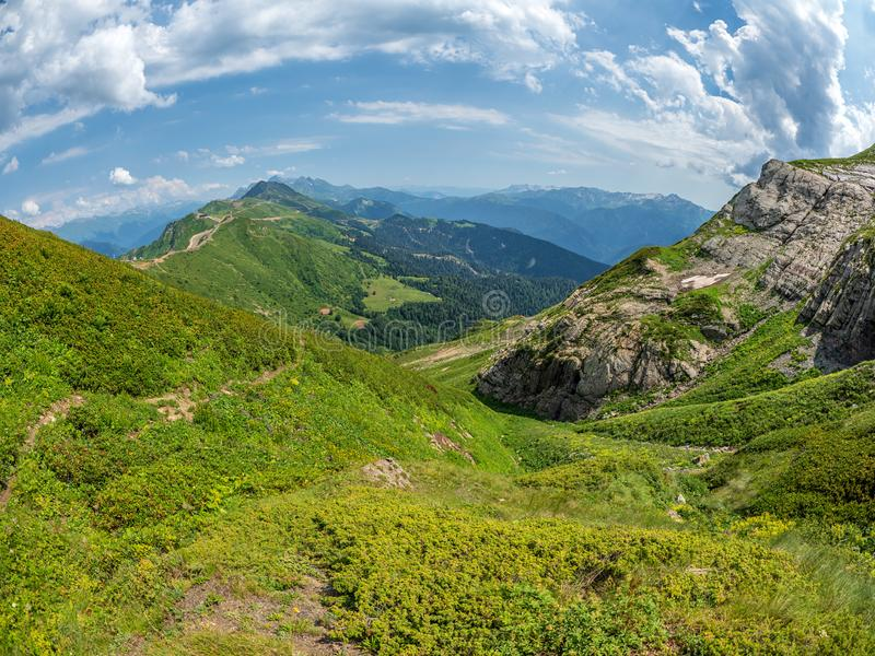 View over the Green Valley, surrounded by high mountains on a clear summer day. Krasnaya Polyana, Sochi, Caucasus. View over the Green Valley, surrounded by high stock image
