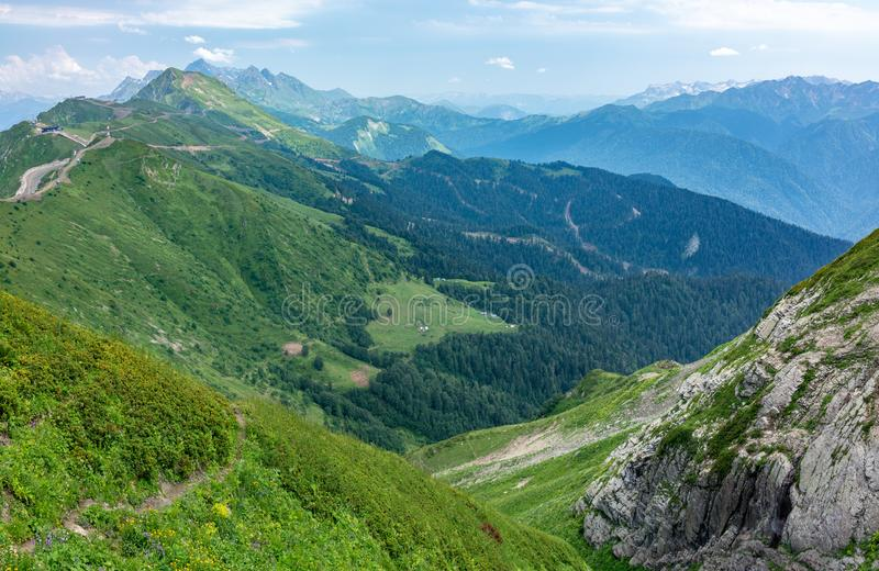 View over the Green Valley, surrounded by high mountains on a clear summer day. Krasnaya Polyana, Sochi, Russia stock photography