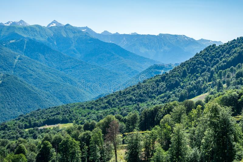 View over the Green Valley, surrounded by high mountains on a clear summer day. Krasnaya Polyana, Sochi, Russia stock images
