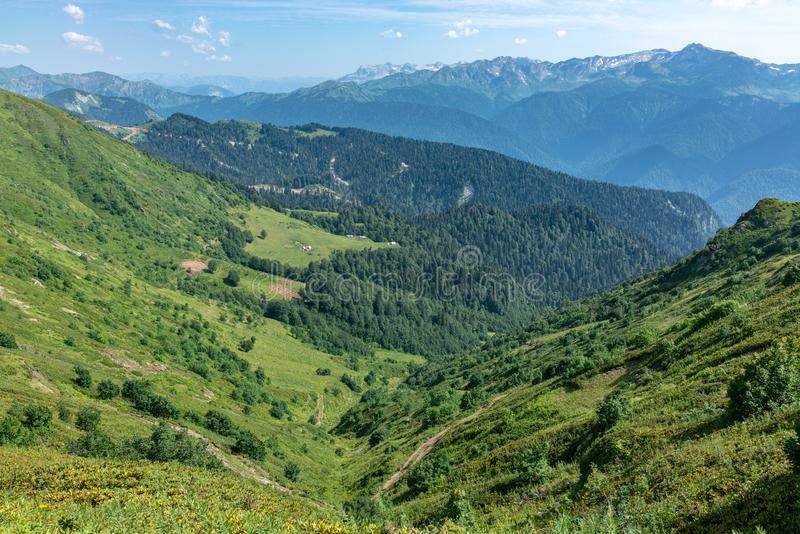 View over the Green Valley, surrounded by mountains vyskokimi on a clear summer day. Krasnaya Polyana, Sochi, Caucasus, Russia. View over the Green Valley royalty free stock images