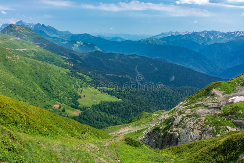 View over the Green Valley, surrounded by mountains vyskokimi on a clear summer day. Krasnaya Polyana, Sochi, Russia royalty free stock photography