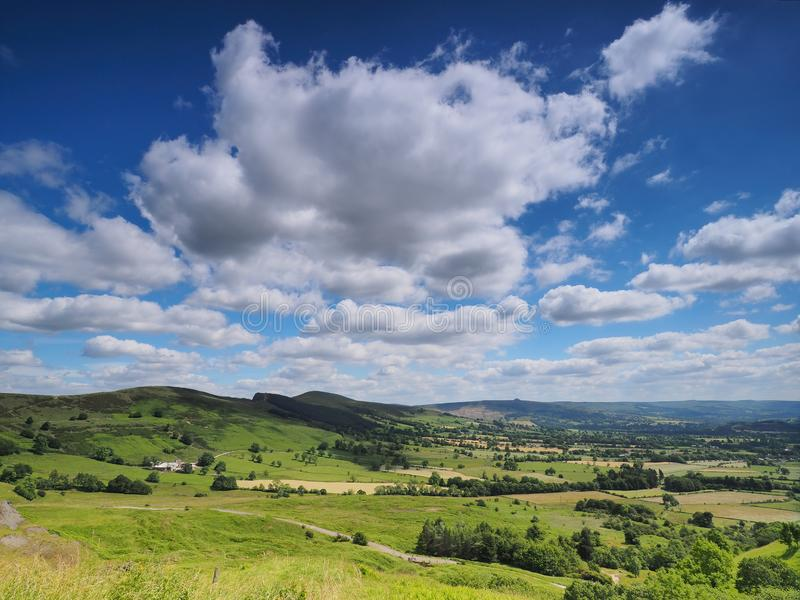 View over Hope Valley and Lose Hill with billowing white clouds and blue sky, Peak District, UK. View over sunlit Hope Valley with Lose Hill in the background stock images