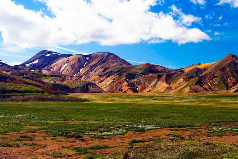 View over lush green plain meadow with bizarr rugged red mountain range. Contrasting with blue sky and cumulus clouds - Landmannalaugar, Iceland royalty free stock photo