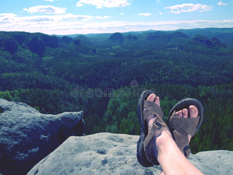 View over own legs to the word. Sandstone rock above valley stock image