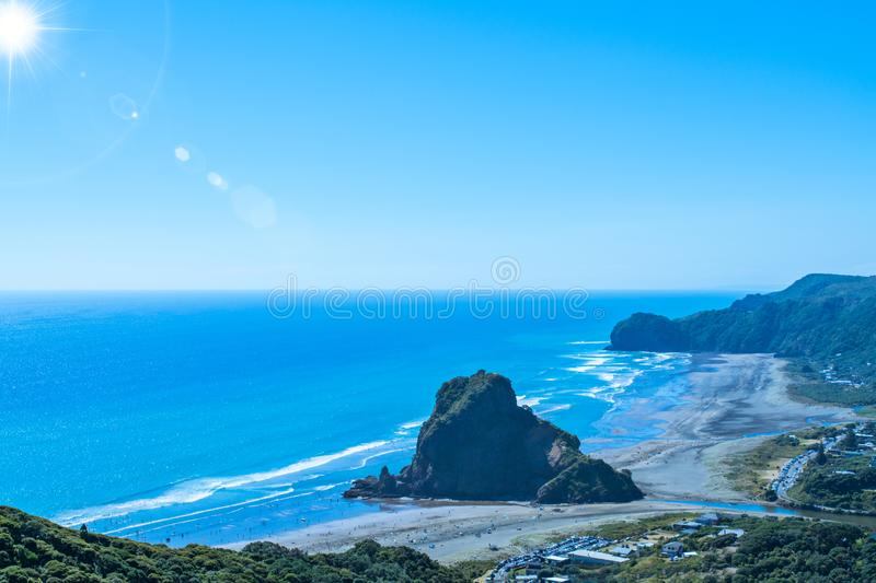 View over Piha beach, mighty Lion Rock in the centre, on the West coast of Auckland, New Zealand. View from a high lokkout over Piha beach, mighty Lion Rock in royalty free stock photos