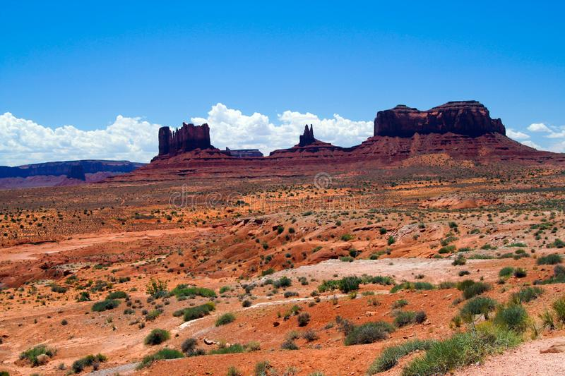 View over red sand dry waste land with green grass tufts on sandstone hills buttes against blue sky - Monument Valley. Utah, Arizona stock photo