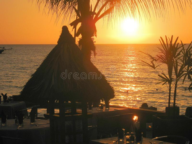 View over restaurant terrace with palm tree and hut with thatched roof on golden sunset over the ocean stock photography