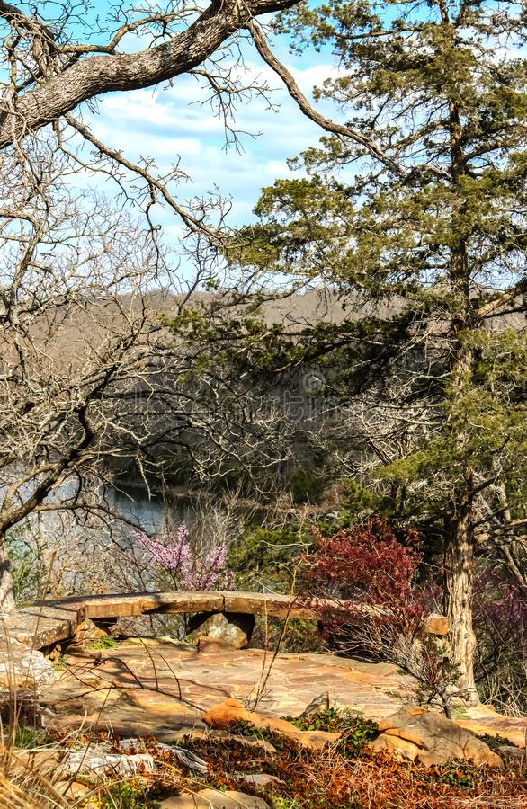View over river and bluffs in early springtime with circular rock bench and resting place stock photos