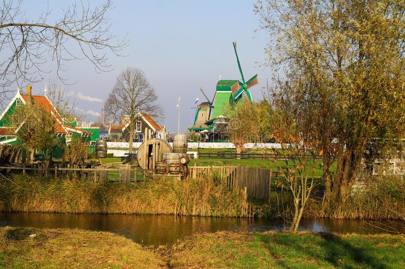 View over river and trees on ancient wind mills in dutch traditional nostalgic village Zaanse Schans, Netherlands. View over river and trees on ancient wind stock photography