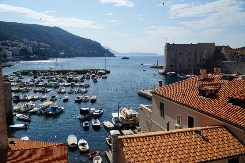Dubrovnik old town. View over roofs in Dubrovnik old town. Boats dockef in harbour. Tile roofs. Sunny day. Clouds in the sky. Blue sea royalty free stock image