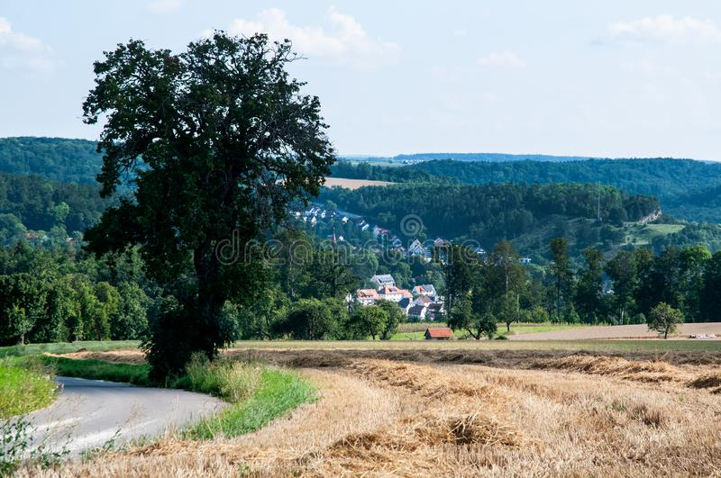 View over rural summer landscape in swabian alb. Summer landscape in swabian alb in southern Germany with bent country road and stubble field royalty free stock photo