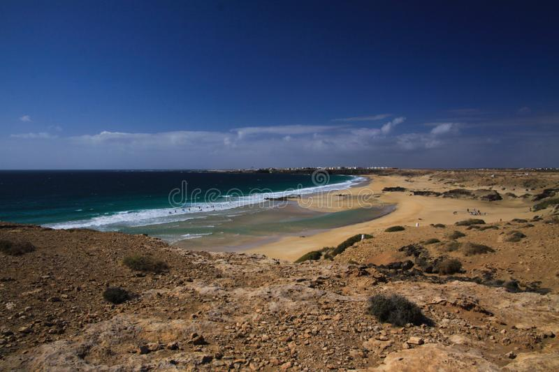 View over sand dunes with green ocean on Playa del Aljibe on white village on steep cliff El Cotillo - North Fuerteventura. View over sand dunes with green ocean stock photo
