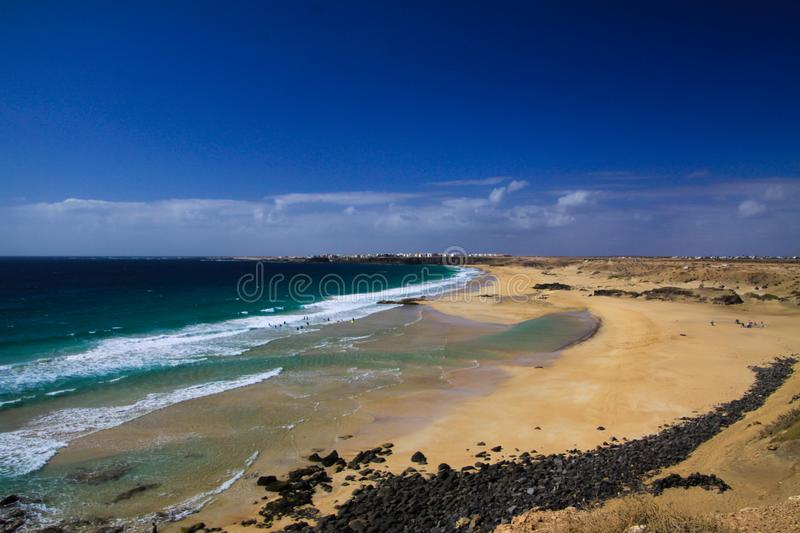 View over sand dunes with green ocean on Playa del Aljibe on white village on steep cliff El Cotillo - North Fuerteventura. View over sand dunes with green ocean stock photos