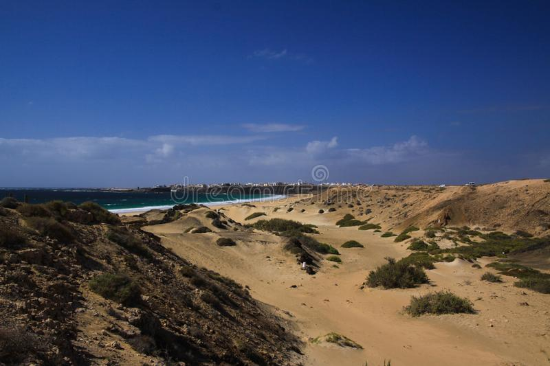 View over sand dunes with green ocean on Playa del Aljibe on white village on steep cliff El Cotillo - North Fuerteventura. View over sand dunes with green ocean stock image