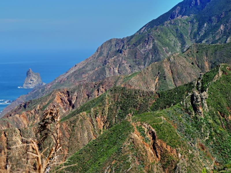 View over the striking, slightly greened ridges of the Anaga Mountains. On the left side blue, smooth Atlantic Ocean and blue sky royalty free stock photo