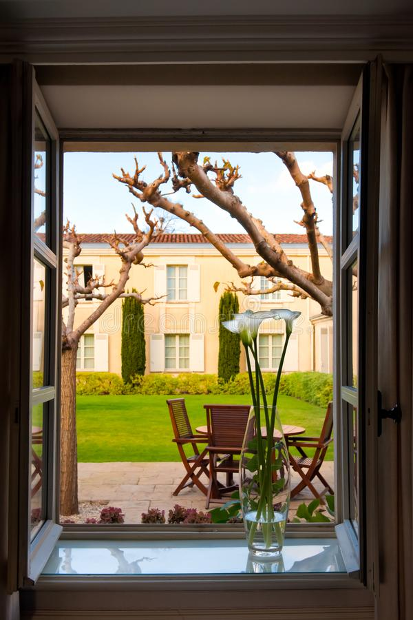 View out of opened window with vase on sill to backyard with patio, formal garden of Chateau Cordeillan-Bages, Bordeaux, France. stock photo