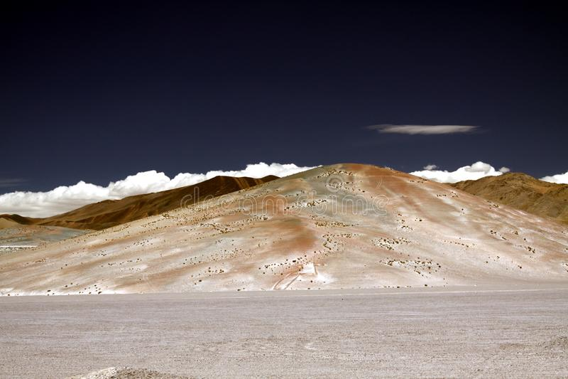 View over white barren salt plain on cone shaped white and brown colored bare mountain contrasting with deep blue sky. Maricunga Salt flat plateau near San stock photos