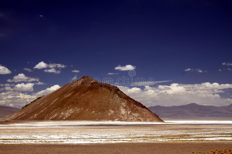 View over white and brown barren plain on  brown bare pyramid shaped hill against blue sky. Maricunga Salt flat plateau near San Pedro de Atacama, Chile royalty free stock images