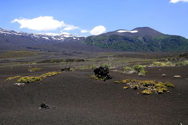 View over wide field of volcanic lava ash on peak of black Volcano Llaima with spots and stripes of snow and ice royalty free stock photography