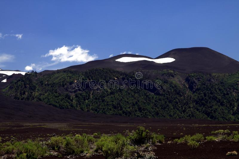 View over wide field of volcanic lava ash on peak of black Volcano Llaima with spots and stripes of snow and ice stock images