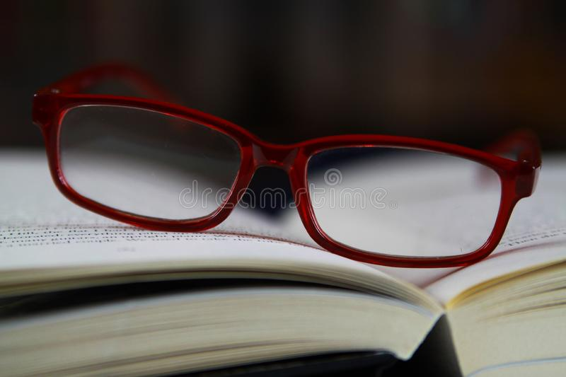 View on pages of open book with red reading glasses stock photography