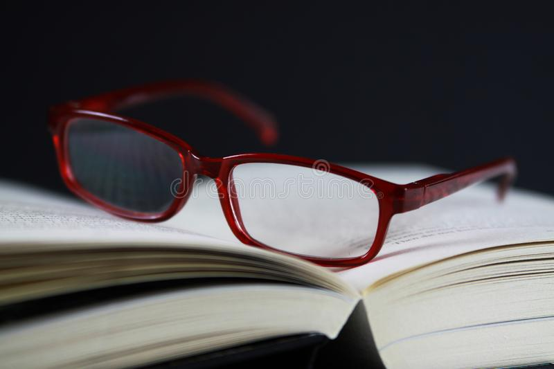 View on pages of open book with red reading glasses royalty free stock images