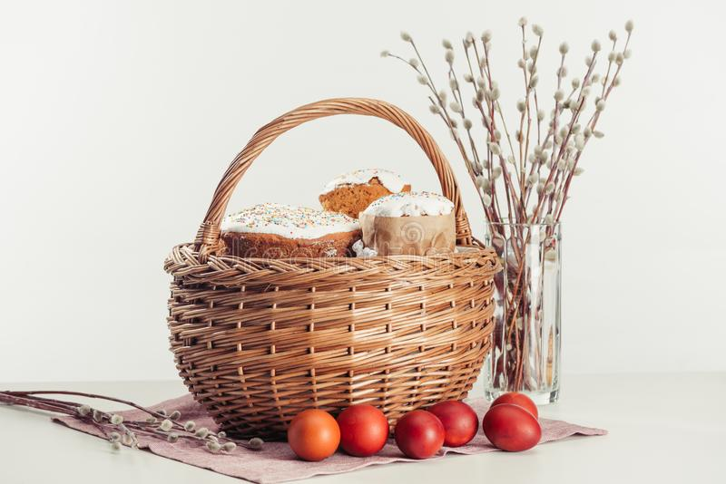 View of painted eggs in basket, willow twigs and delicious easter cakes. Basket with easter cakes, painted eggs and catkins on grey stock image