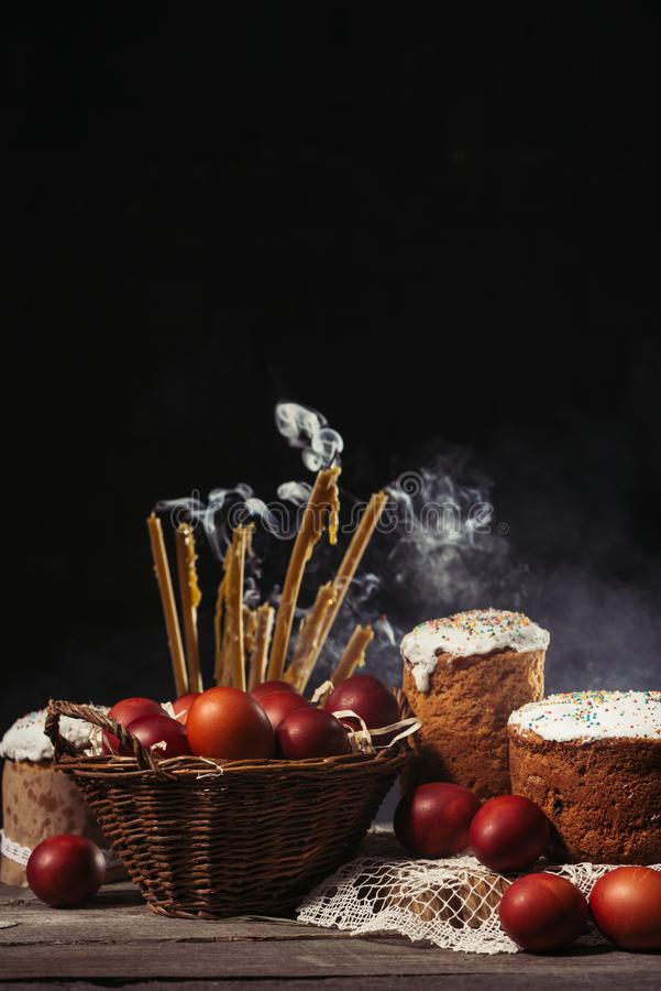 View of painted eggs in basket, willow twigs and delicious easter cakes. Candles with smoke, homemade easter cakes and painted chicken eggs in basket on wooden stock photo