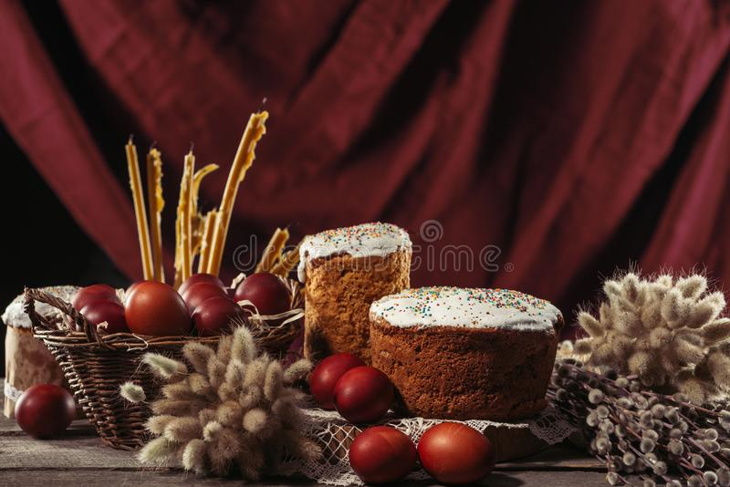View of painted eggs in basket, willow twigs and delicious easter cakes. Close-up view of catkins, candles, easter cakes and painted chicken eggs on table stock photography