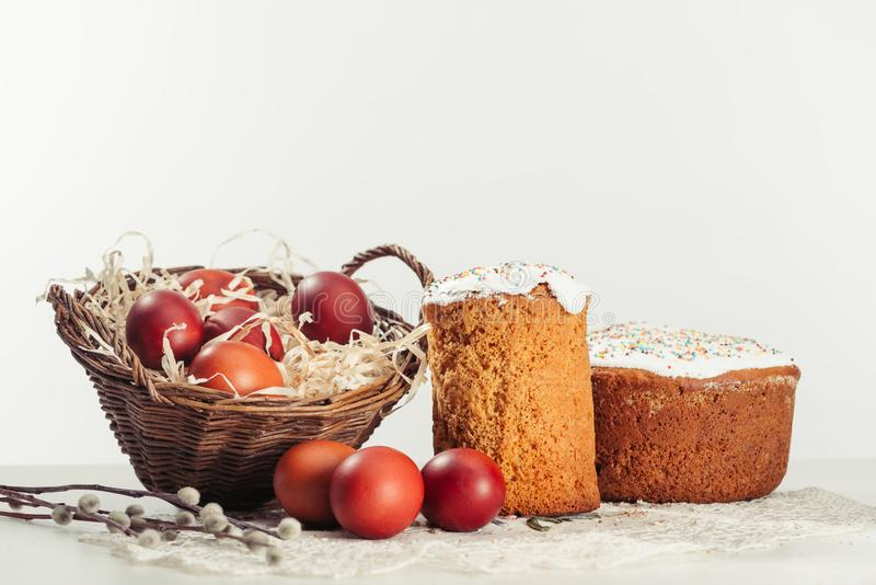 View of painted eggs in basket, willow twigs and delicious easter cakes. Close-up view of painted chicken eggs in basket, willow twigs and easter cakes on grey royalty free stock photography