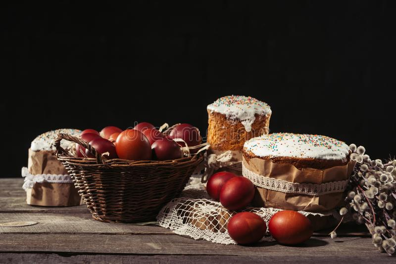 View of painted eggs in basket, willow twigs and delicious easter cakes. Close-up view of painted eggs in basket, willow twigs and delicious easter cakes on royalty free stock photos