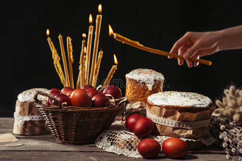 View of painted eggs in basket, willow twigs and delicious easter cakes. Cropped shot of person holding burning candle and easter cakes with painted eggs on stock image