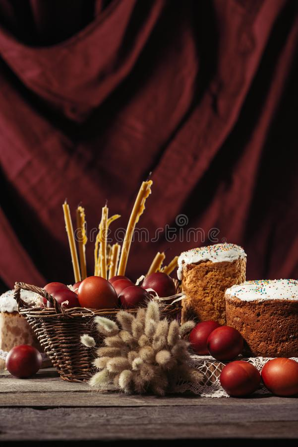 View of painted eggs in basket, willow twigs and delicious easter cakes. Homemade easter cakes, painted chicken eggs and candles on wooden table royalty free stock images