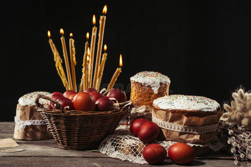 View of painted eggs in basket, willow twigs and delicious easter cakes. Sweet homemade easter cakes, painted chicken eggs and burning candles on table royalty free stock photography