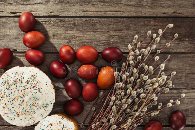 View of painted eggs in basket, willow twigs and delicious easter cakes. Top view of sweet homemade easter cakes, painted chicken eggs and catkins on wooden royalty free stock photo