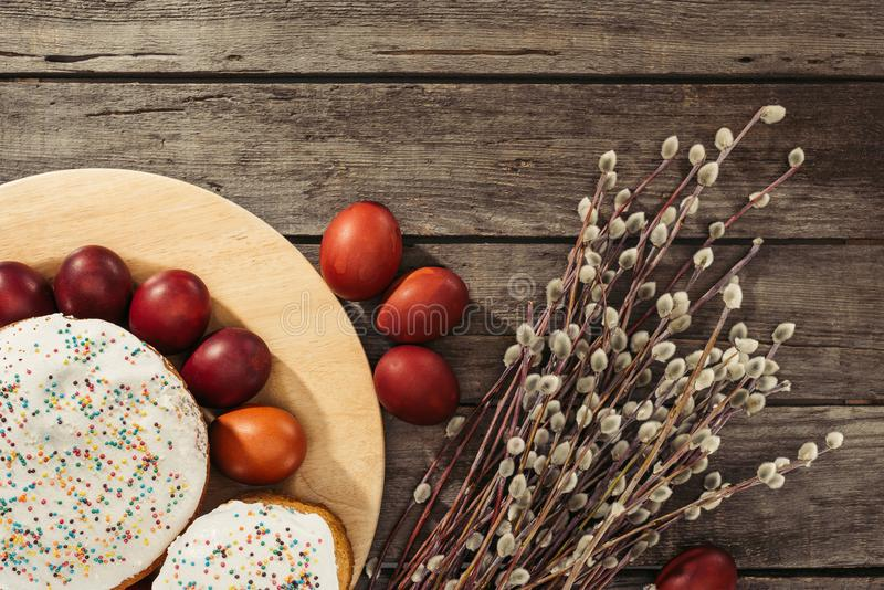 View of painted eggs in basket, willow twigs and delicious easter cakes. Top view of painted chicken eggs, easter cakes and catkins on wooden surface stock photography