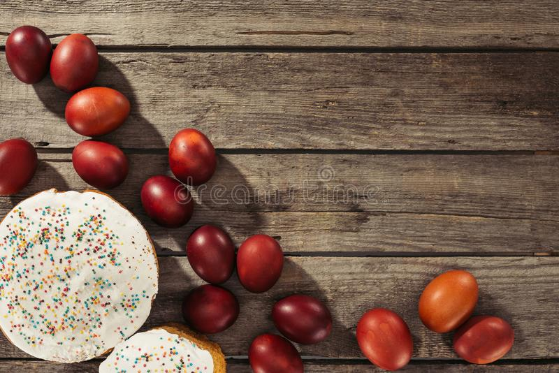 View of painted eggs in basket, willow twigs and delicious easter cakes. Top view of sweet homemade easter cakes and painted chicken eggs on wooden surface stock image