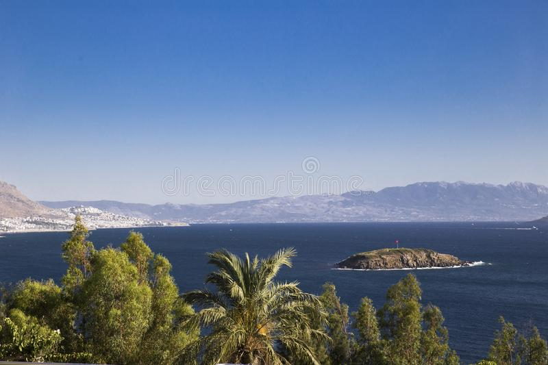 View of the palm trees in the foreground and small islands in th. E sea and mountains in the background in the morning haze royalty free stock images