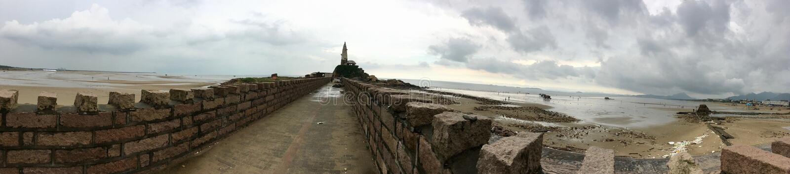 View panorama the old stone wall to the lighthouse in the sea in China. Morning sea landscape on a cloudy rainy day. royalty free stock photos