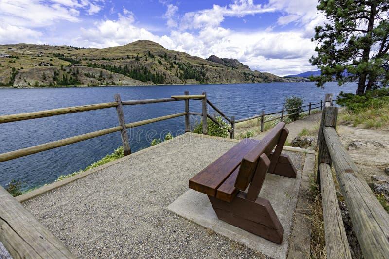 View of a park bench at Kalamalka Lake from Kalamalka Lake Provinial Park near Vernon British Columbia Canada. On a summer day stock photos