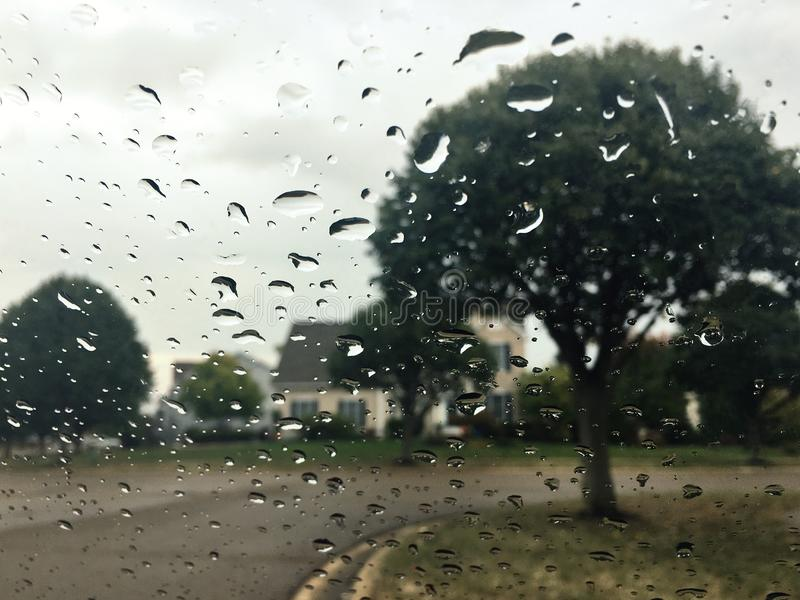 Rainy day in suburbs. Raindrops cover the glass. royalty free stock photography
